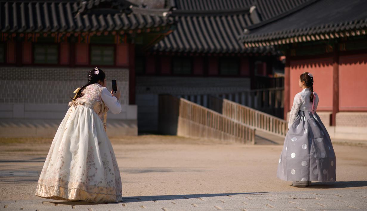 Pengunjung mengenakan pakaian tradisional Hanbok mengambil foto di istana Changdeokgung di Seoul , Korea Selatan (2/4). Korea Selatan sedang bersiap untuk meluncurkan jaringan seluler 5G pertama di dunia pada 5 April. (AFP Photo/Ed Jones)