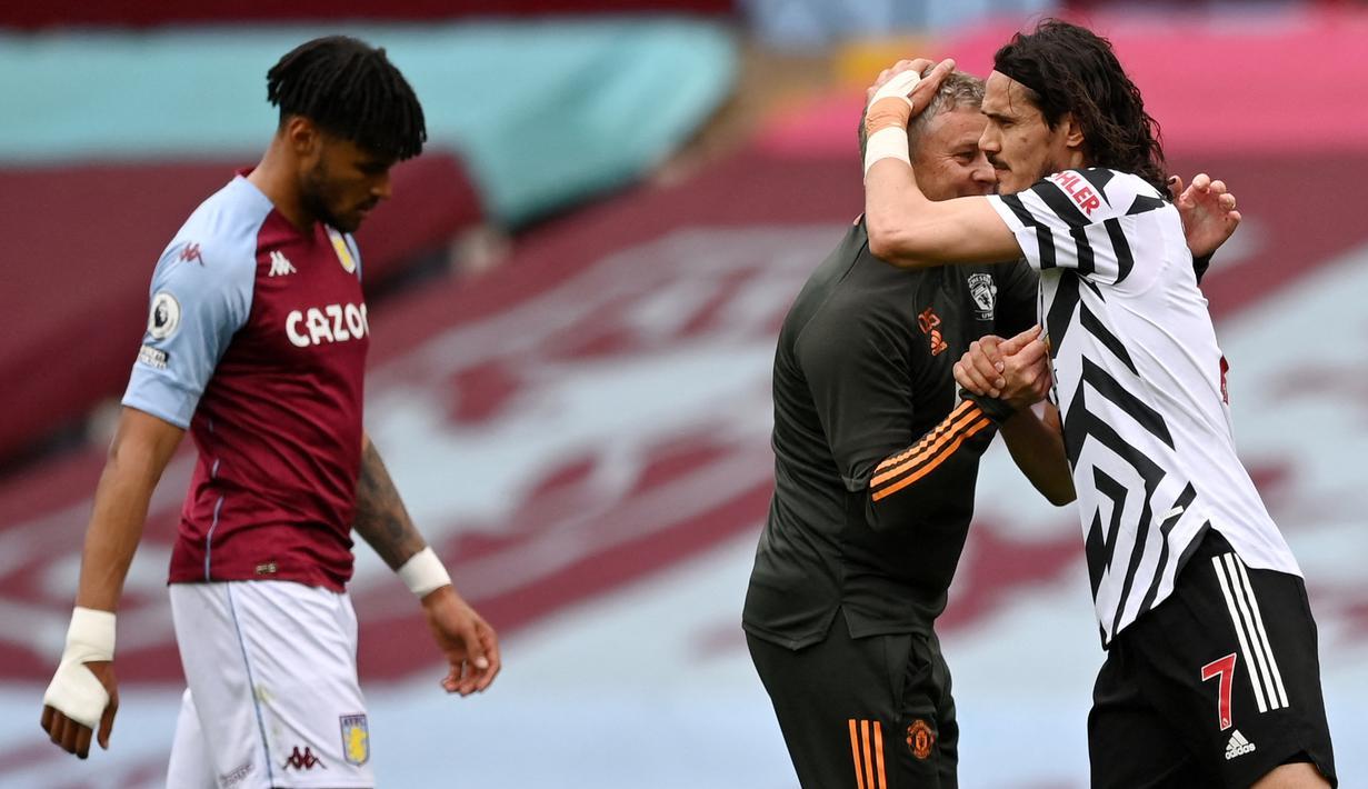 Pelatih Manchester United, Ole Gunnar Solskjaer memberikan selamat kepada Edinson Cavani yang berhasil mecetak gol ke gawang Aston Villa dalam pertadingan lanjutan Liga Inggris 2020/2021. (Foto: AFP/Pool/Shaun Botterill)