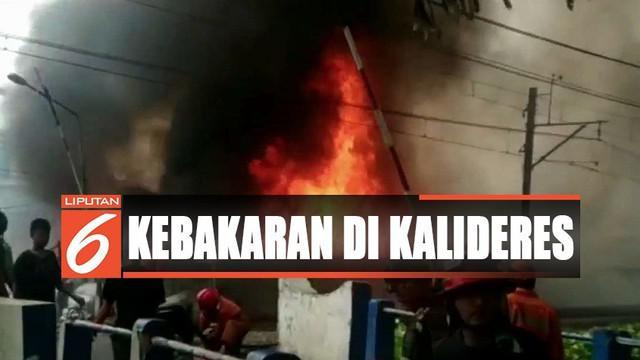 Petugas pemadam kebakaran bersama warga berusaha menjinakan kobaran api yang membumbung tinggi.