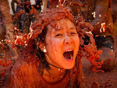 """Seorang peserta bersuka ria dengan tomat yang hancur saat festival tahunan """"Tomatina"""" di Bunol, salah satu kota di timur Spanyol, Rabu (29/8/2019). Digelar sejak 1945, perang tomat ini menjadi daya tarik utama bagi wisatawan mancanegara seperti dari Inggris, Jepang, dan AS. (JAIME REINA / AFP)"""