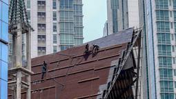 Aktivitas pekerja di atas atap gereja tanpa alat pengaman lengkap, Jakarta, Rabu (12/2/2020). Kemnaker mengatakan tingginya angka kecelakaan kerja di Indonesia disebabkan tidak maksimalnya penerapan K3 yang diatur dalam UU No1 Tahun 1970 tentang Keselamatan Kerja. (Liputan6.com/Faizal Fanani)