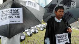 Aktivis dari Gema Tapteng mengenakan payung hitam saat melakukan aksi unjuk rasa di depan gedung KPK, Jakarta, Kamis (26/4). Bakhtiar Ahmad Sibarani dinilai telah memberi suap terhadap mantan  Ketua MK, M Akil Mochtar. (Merdeka.com/Dwi Narwoko)