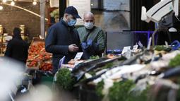 Orang-orang yang memakai masker wajah berbelanja di Borough Market di London selatan selama penguncian nasional (lockdown) ketiga Inggris, Selasa (12/1/2021). Borough Market menjadi tempat pertama yang mewajibkan pemakaian masker di luar ruangan. (AP Photo/Alastair Grant)