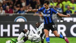 Gelandang Inter Milan, Antonio Candreva, menghindari tekel bek Udinese, Nicholas Opoku, pada laga Serie A 2019/20 di Stadion San Siro, Milan, Sabtu (14/9). Inter menang 1-0 atas Udinese. (AFP/Miguel Medina)