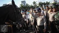 Kapolri Jenderal Tito Karnavian menyapa seorang pasukan polisi berkuda saat Apel Gelar Pasukan Operasi Lilin Jaya 2017 di Lapangan Silang Monas, Jakarta, Kamis (22/12). (Liputan6.com/Faizal Fanani)