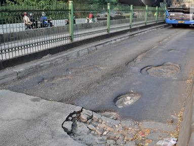 Bus Transjakarta melintas di jalan Galunggung yang rusak dan berlubang di Setia Budi, Jakarta, Selasa (30/7/2019). Jalan yang rusak tersebut mengakibatkan bus melaju dengan kecepatan lambat. (merdeka.com/Iqbal S Nugroho)