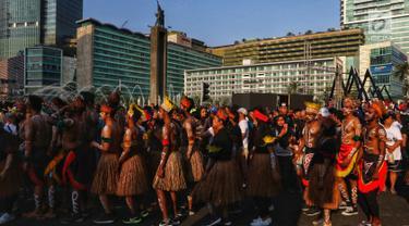 Masyarakat Papua yang tinggal di Jakarta menggelar acara Tari Yospan Massal saat kegiatan Car Free Day di Bundaran HI, Jakarta, Minggu (1/9/2019). Kegiatan yang dihadiri Menkopolhukam Wiranto ini digelar dalam rangka menjalin persatuan dan kesatuan bangsa Indonesia. (Liputan6.com/Johan Tallo)