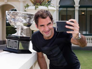 Juara tunggal pria Australia Terbuka Roger Federer dari Swiss berselfie dengan Piala Challenge Norman Brookes di Government House, Melbourne, Australia (29/1). Federer mengalahkan petenis Kroasia Marin Cilic. (Fiona Hamilton/Tennis Australia via AP)