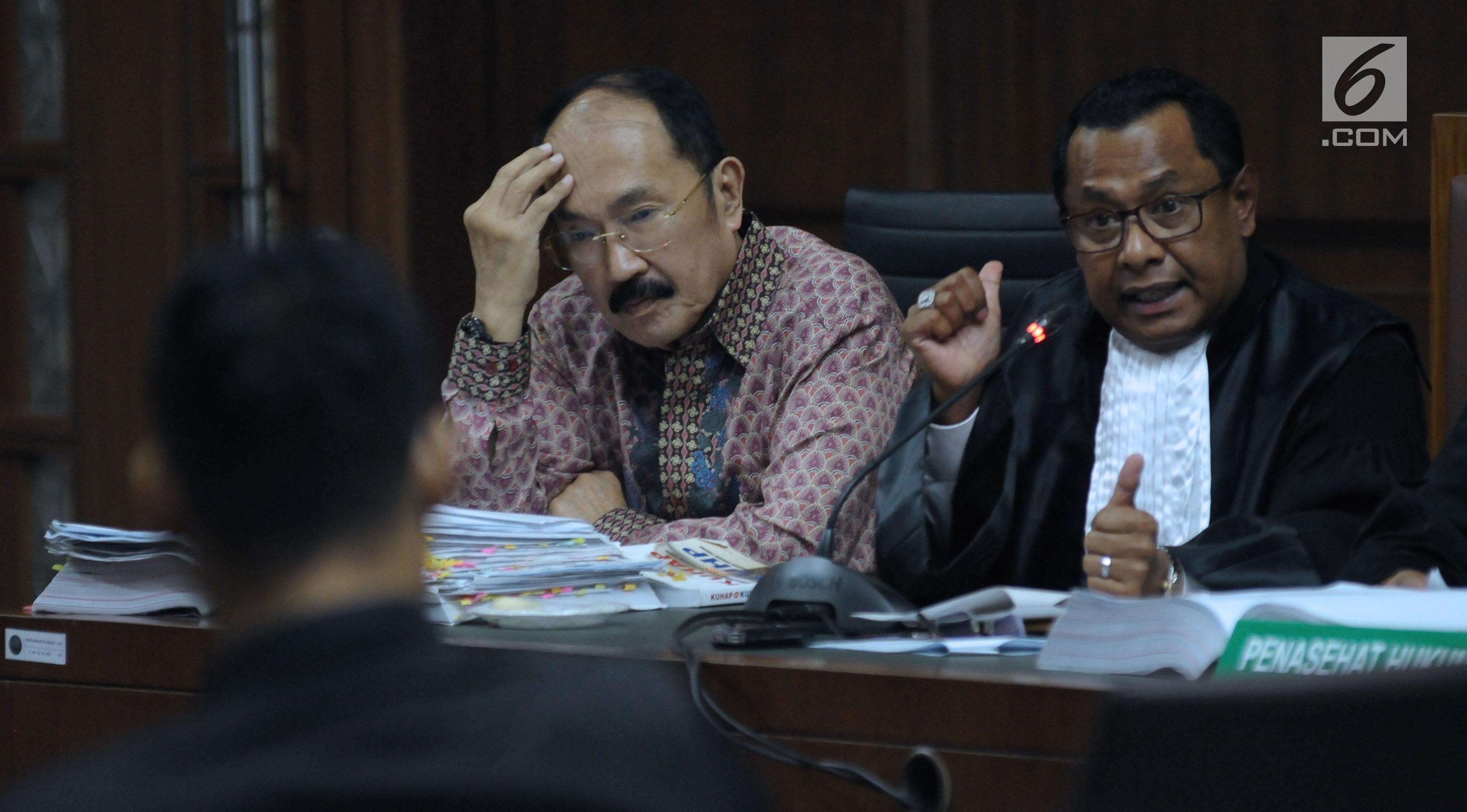 Terdakwa kasus merintangi penyidikan dugaan korupsi e-KTP, Fredrich Yunadi (kiri) menymak keterangan stafnya pada sidang lanjutan di Pengadilan Tipikor, Jakarta, Kamis (12/4). Sidang mendengar keterangan saksi. (Liputan6.com/Helmi Fithriansyah)