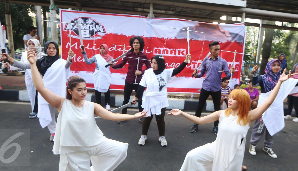 Sejumlah orang yang tergabung dalam relawan Kawan8 dan Mahasiswa IKJ yang menggelar flashmob di Jalan Jenderal Sudirman, Jakarta, Minggu (5/3). Acara tersebut diwarnai aksi teatrikal. (Liputan6.com/Helmi Afandi)