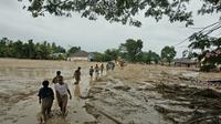 Penduduk desa berjalan melalui daerah banjir di desa Radda di Kabupaten Luwu Utara, Sulawesi Selatan (14/7/2020). Akibat musibah banjir bandang ini setidaknya sekitar 15 orang tewas dan belasan lainnya dinyatakan hilang. (AP Photo)