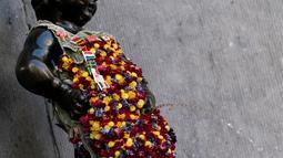 Gambar pada 12 Agustus 2019 memperlihatkan patung 'Manneken Pis' dalam balutan baju bermotif bunga di ibu kota Belgia, Brussels, Senin (12/8/2019). Patung perunggu yang hanya berukuran 60 sentimeter ini berwujud bocah lelaki yang sedang buang air kecil. (Photo by Kenzo TRIBOUILLARD / AFP)