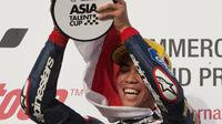 Pebalap Indonesia binaan Astra Honda Racing Team (AHRT), Gerry Salim, mengangkat trofi juara di podium setelah memenangi balapan pertama Asian Talent Cup (ATC) 2016 Qatar di Sirkuit Losail, Sabtu (19/3/2016). (asiatalentcup.com)
