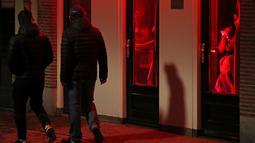 Orang-orang berjalan melewati rumah bordil di Red Light District Amsterdam, Belanda, Rabu (3/4). Pemerintah Amsterdam melarang tur prostitusi di kawasan tersebut karena banyak keluhan dari pekerja seks komersial (PSK). (REUTERS/Yves Herman)
