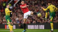 Gelandang Manchester United, Nemanja Matic, berebut bola dengan bek Norwich, Max Aarons, pada laga Premier League di Stadion Old Trafford, Manchester, Sabtu (11/1). MU menang 4-0 atas Norwich. (AFP/Oli Scarff)