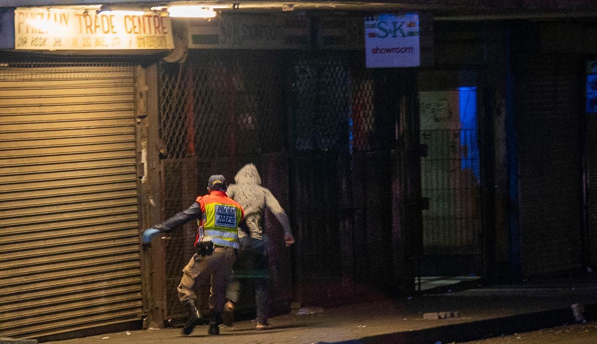 Seorang perwira polisi mengejar seorang pria saat berpatroli di pusat kota Johannesburg, Afrika Selatan, Jumat (27/3/2020). Polisi dan tentara mulai berpatroli beberapa saat setelah Afrika Selatan melakukan Lockdown 21 Hari dalam upaya untuk mengurangi penyebaran Covid-19. (AP Photo/Jerome Delay)