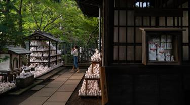 Gambar pada 25 Juni 2019 memperlihatkan seorang pengunjung mengambil gambar patung-patung kucing yang disebut maneki-neko di kuil Gotokuji, Tokyo. Kuil Gotokuji terkenal karena dipercaya sebagai tempat kelahiran maneki-neko, kucing pemberi isyarat yang menjadi jimat keberuntungan. (AP/Jae C. Hong)
