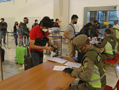 Petugas sedang mengecek SIKM di terminal 3 kedatangan domestik bandara Soekarno Hatta, Tangerang, Banten, Rabu (27/5/2020). Bandara Soetta memberlakukan Tiga checkpoint di terminal kedatangan salah satunya pemeriksaan SIKM dan doukumen kesehatan setiap penumpang. (Liputan6.com/Herman Zakharia)