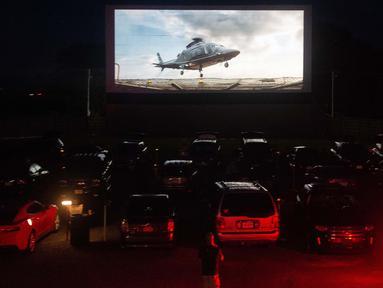 Puluhan mobil terparkir di depan layar bioskop saat pemutaran film drive-in di Family Drive-in di Virginia, 10 Agustus 2018. Menonton film di luar ruangan atau drive-in merupakan bagian penting dalam industri hiburan di Amerika. (AFP PHOTO/Nicholas Kamm)