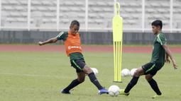Pemain Timnas Indonesia U-22, Dallen Doke, berebut bola dengan Firza Andika, saat latihan di Stadion Madya, Senin (21/1). Pemain yang pernah merumput di Spanyol ini bertekad menembus skuat utama untuk tampil di Piala AFF U-22. (Bola.com/M Iqbal Ichsan)