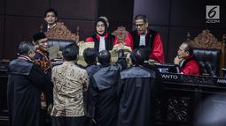 Komisioner KPU, Hasyim Asyari mengantar amplop kehadapan Majelis Hakim dan mendeskripsikan perbedaannya dalam sidang sengketa pilpres 2019 di Gedung MK, Jakarta, Kamis (20/6/2019). Hasyim mengatakan, ada kode-kode tertentu di tiap amplop yang menunjukkan fungsinya. (Liputan6.com/Faizal Fanani)