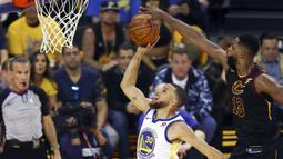 Pemain Cavaliers, Tristan Thompson (13) melakukan blok tembakan pemain Warriors, Stephen Curry (30) pada gim pertama final NBA basketball di Oakland, California, (31/5/2018). Warriors menang 124-114. (AP/Ben Margot)