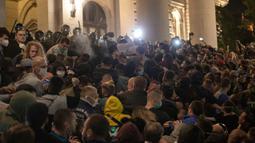 Aparat kepolisian menggunakan semprotan merica untuk membubarkan demonstran di depan parlemen Serbia di Beograd, Selasa (7/7/2020). Ribuan pengunjuk rasa marah setelah pemerintah mengeluarkan keputusan untuk memberlakukan kembali jam malam akibat melonjaknya kasus Covid-19. (AP/Marko Drobnjakovic)