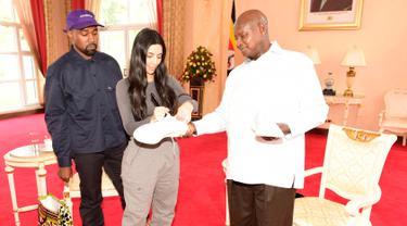 Foto yang dirilis kantor kepresidenan Uganda memperlihatkan Presiden Yoweri Museveni menerima hadiah sepasang sepatu kets dari penyanyi rap AS, Kanye West dan istrinya Kim Kardashian di Entebbe, Senin (15/10).(AFP/UGANDAS PRESIDENTIAL PRESS OFFICE)
