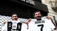 Suporter memperlihatkan jersey Juventus atas nama Cristiano Ronaldo di depan toko resmi klub di Turin, Selasa (10/7). Ronaldo akan diperkenalkan secara resmi ke publik sebagai pemain Juventus pada Senin depan. (AFP PHOTO / Isabella Bonottovv)
