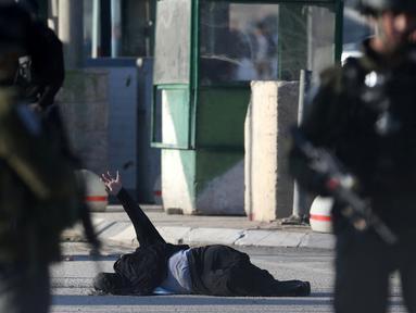 Seorang wanita Palestina terlihat kesakitan usai tertembak oleh polisi Israel di Qalandiya pos pemeriksaan dekat kota Ramallah, Tepi Barat (30/12). Menurut keterangan petugas, wanita tersebut mencoba menusuk salah satu polisi. (Reuters/Mohamad Torokman)