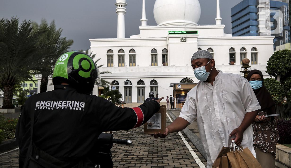 Petugas membagikan takjil kepada pengendara secara drive thru di Kompleks Masjid Al-Azhar, Jakarta, Kamis (15/4/2021). Pengelola masjid menyiapkan 500 bungkus takjil setiap harinya untuk pengendara yang dibagikan dengan sistem drive thru untuk mencegah penyebaran COVID-19. (Liputan6.com/Johan Tallo)