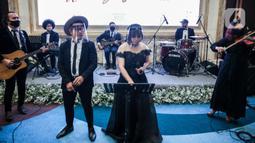 Band pernikahan mengenakan face shield saat simulasi penerapan protokol kesehatan resepsi pernikahan di era new normal di Jakarta, Kamis (9/7/2020). Kegiatan ini bertujuan untuk mengedukasi masyarakat dalam acara pernikahan guna mencegah penyebaran COVID-19. (Liputan6.com/Faizal Fanani)