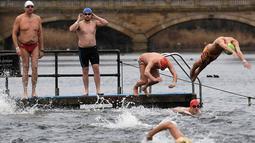 Peserta meluncur ke danau saat mengikuti lomba berenang di Danau Serpentine di Hyde Park, London, Inggris, Minggu (25/12). Lomba berenang di danau yang dingin ini sudah menjadi acara tahunan setiap perayaan natal. (REUTERS/Toby Melville)