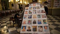 Pekerja memegang panel kayu setelah menempelinya dengan potret korban meninggal akibat virus corona di dalam Katedral, di Lima, Peru pada 13 Juni 2020. Misa Minggu di Katedral Lima dihadiri lebih dari 4.000 potret mereka yang telah meninggal dalam pandemi Covid-19 yang menyebar di Peru. (AP Photo/Ro