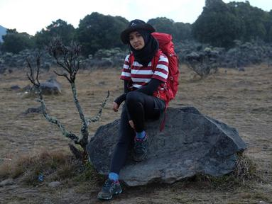 Penampilan Arafah cukup santai saat mendaki Gunung Gede. Berpose di sebuah batu besar, runner up SUCA 2 ini menggunakan baju kaus belang berwarna merah putih dan celana hitam, gayanya saat naik gunung sangat meyakinkan.  (Liputan6.com/IG/@arafahrianti)