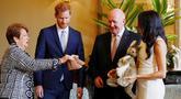 Pangeran Harry dan Meghan Markle bereaksi ketika menerima hadiah dari Gubernur Jenderal Australia Sir Peter Cosgrove dan istrinya, Lady Cosgrove di Sydney, Selasa (16/10). Meghan tampak senang menerima hadiah bayi pertamanya. (Phil Noble/Pool via AP)