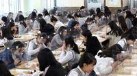 Siswa senior makan siang di meja yang dilengkapi dengan pembatas plastik untuk mencegah penyebaran virus corona baru di kafetaria di Jeonmin High School di Daejeon, Korea Selatan, Rabu, (20/5/2020). (Kim Jun-beom/Yonhap via AP)