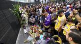 Fans Kobe Bryant berduka saat berkumpul di depan Staples Center, rumah Los Angeles Lakers (26/1/2020). Legenda NBA dan Los Angeles Lakers Kobe Bryant meninggal dunia akibat kecelakaan helikopter di Calabasas, California, Minggu 26 Januari waktu setempat. (AP Photo/Matt Hartman)