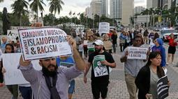Pengunjuk rasa menolak kebijakan Trump yang membatasi imigrasi dari beberapa negara Timur Tengah dan Afrika masuk ke AS, Miami, Kamis (26/1). (AP Photo / Alan Diaz)
