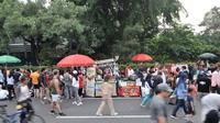 Pedagang kaki lima (PKL) berdagang di badan jalan saat car free day di kawasan Bundaran HI, Jakarta, Minggu (18/11). Kurangnya pengawasan menyebabkan PKL mengganggu kenyamanan warga berolahraga. (Merdeka.com/Iqbal S. Nugroho)