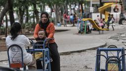 Orang tua mendampingi anak bermain di taman kawasan Duren Sawit, Jakarta, Kamis (26/11/2020). Bermain dengan pendampingan orang tua menumbuhkan potensi kecerdasan secara optimal anak serta menurunkan frekuensi terjadinya stunting, terutama pada balita usia 2-3 tahun. (merdeka.com/Iqbal S. Nugroho)