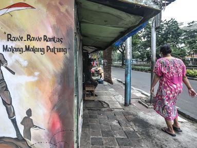 Warga melintas di depan mural bertemakan Pancasila di Kampung Pancasila kawasan Galur, Johar Baru, Jakarta, Selasa (1/6/2021). Kelurahan Galur membuat Kampung Pancasila yang dihiasi mural sebagai bentuk mengingatkan masyarakat akan Pancasila sebagai dasar negara. (merdeka.com/Iqbal S. Nugroho)