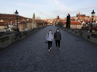 Dua pria muda yang mengenakan masker berjalan melintasi Jembatan Charles yang sepi di Praha, Republik Ceko, Senin (16/3/2020). Pemerintah Ceko memberlakukan pembatasan terhadap seluruh warganya dalam upaya mengendalikan penyebaran virus corona COVID-19. (AP Photo/Petr David Josek)