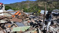 Seorang pria menyelamatkan sisa-sisa puing dari bangunan rumah yang rusak di Menggala, Lombok Utara, Rabu (8/8). Warga terdampak gempa Lombok mulai mengamankan barang berharga miliknya karena kuatir dijarah pihak tidak bertanggung jawab. (AFP/ADEK BERRY)