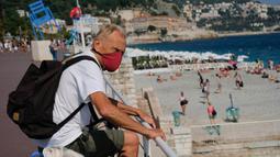 Seorang pria yang memakai masker mengunjungi sebuah pantai yang ada di Nice, Prancis selatan, pada Rabu (22/7/2020). Banyak pengunjung memadati Nice selama liburan musim panas di tengah pandemi COVID-19. (Xinhua/Serge Haouzi)