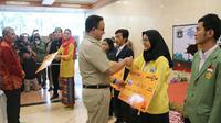 Gubernur DKI Jakarta Anies Baswedan menyerahkan Kartu Jakarta Mahasiswa Unggul.