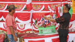 Pembeli melihat bendera dan umbul-umbul yang dijajakan pedagang di pinggir trotoar kawasan Pasar Minggu, Jakarta, Kamis (2/8). Beberapa penjual bendera menawarkan dagangannya seharga Rp15.000-Rp400.000 tergantung ukuran.  (Liputan6.com/Herman Zakharia)