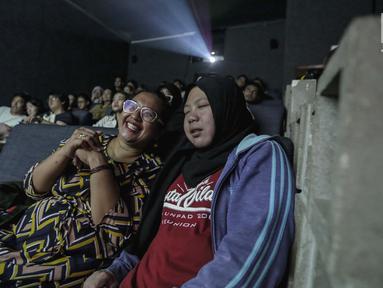 Sejumlah penyandang tunanetra mendengarkan relawan bisik saat menyaksikan film di Bioskop Bisik di Pavilliun 28, Jakarta, Minggu (14/1).  Kini, menonton bioskop bukan menjadi hal mustahil lagi bagi penyandang tunanetra. (Liputan6.com/Faizal Fanani)