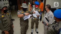 Satpol PP Tangerang Selatan melakukan pendataan terhadap para tamu yang menginap di Hotel Reddoorz, BSD, Serpong, Jumat (21/08/2020). Satpol PP mengamankan sejumlah pasangan bukan suami istri dalam sebuah operasi di hotel-hotel ketika Pemkot Tangsel memperpanjang PSBB. (merdeka.com/Dwi Narwoko)
