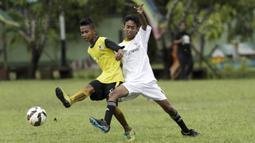 Pemain SSB Tulehu Putra berusaha melewati pemain Galunggung FC pada semifinal turnamen Liga Remaja UC News di Lapangan Masariku Yonif 733, Ambon, Rabu (29/11/2017). (Bola.com/Peksi Cahyo)